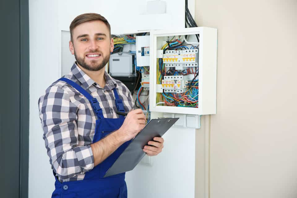Male electrician with clipboard near fuse board indoors, space for text; how to become an electrician; amps vs watts vs volts